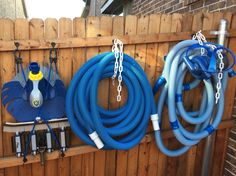 Coat hooks, bungees and plastic chains make for tidy pool equipment storage.
