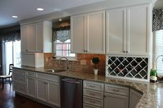 A remodeled kitchen in Chalfont, Pennsylvania, now has maximum space and an organized wine collection. Kristin Filosa of LA Kitchens & Baths specified Fieldstone Cabinetry's Stratford door style in Maple, and chose the five-piece construction option for the drawer headers. The classic White finish brightens up the open space and complements the natural lighting. This kitchen includes a lift up appliance garage that conceals two coffee machines and a toaster.