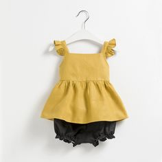 Este conjunto tan alegre y veraniego está compuesto por unas bermudas gris marengo y una camiseta amarilla con volantes en los tirantes. ¿Qué te parece para tu niña?