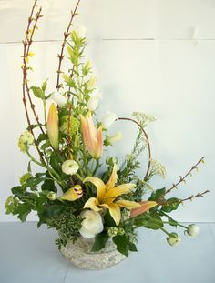 Blooming branches of Forsythia frame an arrangement of lilies, ranunculus, rice flower