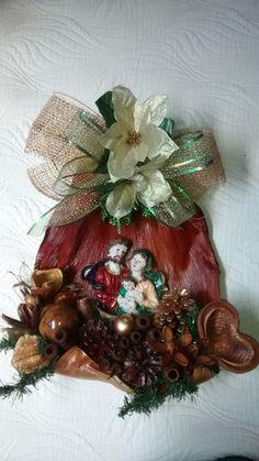 Arranjo de natal para dependurar em porta ou parede, feito de palha de coqueiro envernizada, com fitas,juta importada,bicos de papagaio,bolas natalinas,arranjos natalinos,sagrada família de resina,diversas sementes da natureza secas envernizadas ou pintadas. R$ 135,00