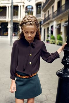 chic kids style with a black button up wrap blouse, emerald mini skirt and tortoiseshell belt