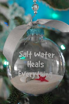 Weve taken our favorite quote, Salt water Heals Everything, and added it in vinyl to an acrylic ornament. Perfect for anyone who loves the ocean! The lettering is done in white vinyl and weve added turquoise glitter to the top. Comes with sand, seashells, a little red starfish and a crystal swirled ornament hook. Comes just as shown.  Ornament is round and flat and 4 wide and 1 3/4 deep.  This listing is for ONE ornament.