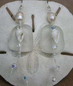 Seaglass earrings--translucent white seaglass  suspended from a  freshwater pearl with natural white nassa shell, and Swarovski crystals.
