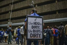 "A political demonstrator mocks Zuma's ""shower"" comments"