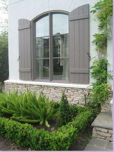 Sally Wheat, boxwoods, foxtail fern, gray shutters, stone