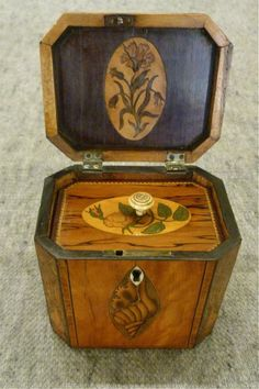 A good quality late 18th century SATINWOOD TEA CADDY of cube form. The front and the lid are inlaid with navette shaped panels of conch shells, within narrow crossbanding, whilst the front canted corners are beautifully inlaid with marquetry bowls of flowers.  The interior is further inlaid  to the underside of the lid and the inner lid is similarly marquetry inlaid