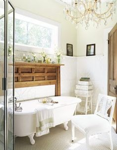 Nicnac Maniac - A fireplace mantel creates a focal point frame around the claw foot tub in this romantic shabby chic style bathroom.   Love the mix of natural woods and white painted furniture.