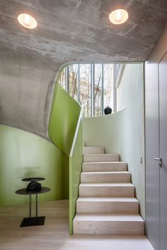 One of the tall voids contains the staircase, which features a sweeping green balustrade and timber treads. Its underside displays the cast concrete used to form its structure.