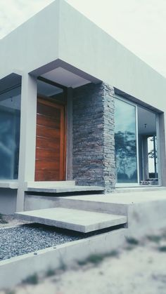 Mirá imágenes de diseños de Casas de estilo minimalista en gris: Ingreso . Encontrá las mejores fotos para inspirarte y creá tu hogar perfecto.