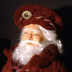 """Marguerite Taylor - Close-up of 24"""" Father Christmas. He wears a rich burgundy coat and matching hat over a cotton tunic. He,s sculpted from polymer clay over a wire armature. The hair and beard are 100% mohair and the eyes are hand-painted. All dolls, toys and accessories that accompany her Santas are hand-crafted by Marguerite."""
