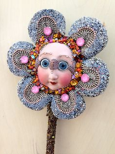 Mae is a wall-hanging flower who likes to watch over her friends lovingly. This flower was covered using Czech rhinestone chain, vintage glass