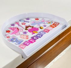 Toddler Tray - Girl $39.95 •  • Nontoxic 100% food-grade melamine.  • Fits perfectly over the table edge.  • Unique non-slip design.  • Well-designed lip catches spills, even liquid!  • Easy to clean and dishwasher safe.  • Educational graphics embedded, so won't fade or peel.  • Durable enough to last generations.  • Light and portable enough to be a travel tray.  • Designed to engage and educate your toddler.  • Ideal for containing playtime mess, too.