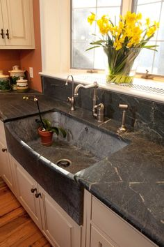 Cut from a single piece of stone, the bow-slant sink from Bucks County Soapstone fits seamlessly into the soapstone countertop.