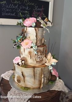 Birch bark tree stump wedding cake with flowers and hummingbirds.