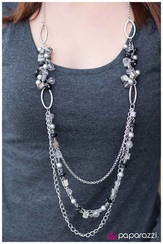 Clusters of clear crystals, gray pearls, iridescent shell pieces, and faceted black beads connect draping strands of silver chain and a strand of accents matching the same pieces of the clusters. Features an adjustable clasp closure.  Sold as one individual necklace. Includes one pair of matching earrings.