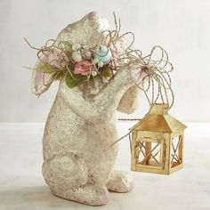 Springtime shimmer is here courtesy of our beautiful bunny adorned with a hand-laid layer of naturally luminous capiz shell. Adding to the shimmer, she holds a golden lantern aloft while wearing a gorgeous garland of springtime flowers.