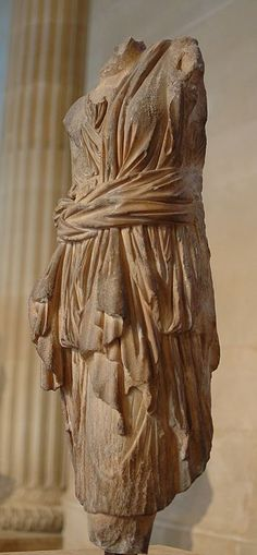 Artemis. Pentelic marble. Roman 1st–2nd C. CE,  Artemis is identified  by her himation (coat) thrown over the left shoulder and girded around the waist,  and chiton (tunic) rolled up for running.