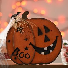 Add a little fun to your spooky Halloween decor with the Boo Carved Wooden Jack O' Lantern.