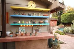 Colorful shelves in a Southwest themed garden make it cheery even in winter.