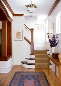 The small space of this cozy entry was opened up by using a partial wall into th. Stained Wood Trim, Oak Wood Trim, Wood Stain, Dark Trim, White Trim, White Wood, White Walls, White Baseboards, Baseboard Trim