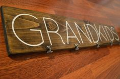 Wood GRANDKIDS Sign, hand crafted and stained. The perfect gift for grandparents!! Comes with clips attached to hang pictures from. Will be shipped ready to hang! - Different font options available, send a message for more information! Size is 6 x 32 Stain is walnut by Minwax.