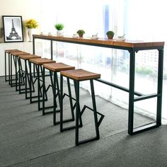 High table with metal frame and rustic woodblock bar top. Matching stools with footrest.