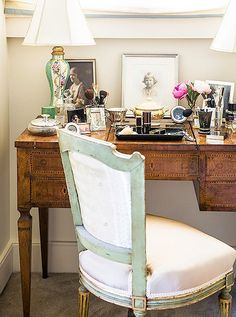 An antique vanity is dressed with family portraits and a pair of hand-painted table lamps.