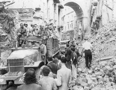 A truck carrying American troops moves through a rubble-filled street in Naples.