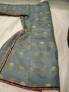 TM108.jpg - Persian silk qaba (coat) folded in half.  Part of the sleeve and armpit are open and feature fabric applique trim.  c. 1600.