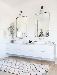 Custom mirrors and vintage lights hang above the vanity in the master bathroom. A small artwork personalizes the space.