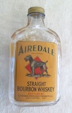 "Airedale Straight Bourbon Whiskey bottle. 1/2 pint Flask Bottle from Standard Distillers in Baltimore Maryland. The bottle stand's approx. 6 3/4"" tall. Back Label: ""Dog Gone Good Whiskey"". c. 1938"
