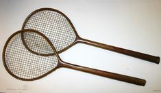 Pair of Edwardian badminton wooden rackets c1910/1915 – fitted with concaved wedges finally grooved handles each with their leather butt caps and one with leather – both retaining good shape c/w original stringing