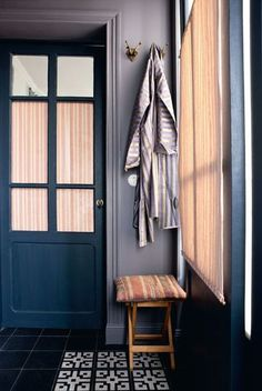 A little bathroom with a blue old door and a black stone floor