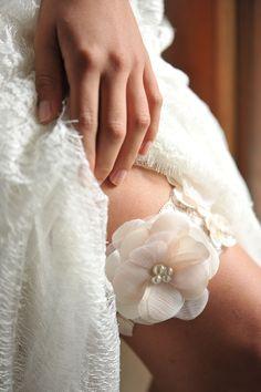 Liga de renda de elastano Lucy, com aplique de uma linda flor redonda feita em cetim e chiffon, com delicadas mini pérolas achatadas R$ 190,00.
