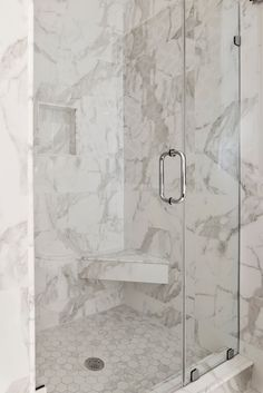 """This walk-in shower in the Master Bath features glazed porcelain tile, 10 x 24 large format size for the walls and a 2"""" hex tile shower floor. Looking closely, we see the edges of the niche, rolled front of the step-in and shower seat - these pencil liners complete the look, in Calacatta Gold Marble! The beauty is in the details."""
