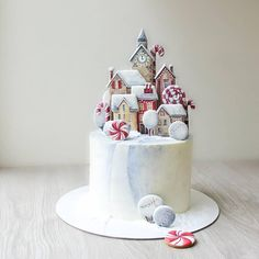 A white cake garnished with sugar biscuit figurines that are forming a lovely snowy town. Perfect Christmas decoration that is also nice for any winter festive event. Christmas Candy, Christmas Desserts, Christmas Treats, Christmas Baking, Christmas Cake Designs, Christmas Cake Decorations, Holiday Cakes, Cow Cakes, Cupcake Cakes