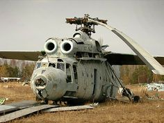 An unusable military helicopter rests in a field.