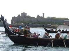 Viking reenactors row longships past Peel castle, on the Isle of Man.