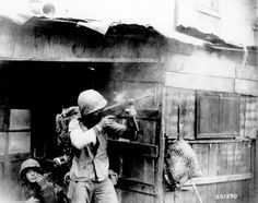 A member of the United Nations troops fires a submachine gun on Communist-led North Korean forces, during fighting in streets of Seoul.   20 September 1950.  Korea.