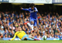 Chelsea playmaker Willian flies through the air after evading the sliding challenge of Cry...
