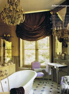 Where to start complimenting this design - 1) quirky lovely architecture: angles, wainscoting, huge window. 2) opulent chandelier 3) brown silk (?) shade 4) that tub and wash sink 5) gilded lavender chair. Enough for now!