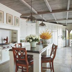 The Christopher Peacock kitchen and counter stools make a traditional statement. The ceiling's stain resembles weathered driftwood, keeping the ambience rustic, causal and beachy. The chrome pendants over the island are from RH; the sinks and faucets are by Rohl.
