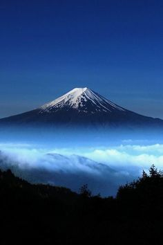 """Rising above the clouds, Mount Fuji, Japan. Fuji-san has long been a sacred mountain. Japanese Buddhists believe the mountain is the gateway to a different world. Mount Fuji, Mount Tate, and Mount Haku are Japan's """"Three Holy Mountains. Monte Fuji, Places Around The World, Around The Worlds, Beautiful World, Beautiful Places, Amazing Places, Beautiful Scenery, Mount Fuji Japan, Amazing Nature"""
