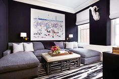 In the den, the walls are upholstered in a dark navy moleskin by Holland & Sherry, and the U-shaped sofa is from A. Rudin.