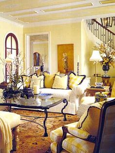 Yellow walls with deeper gold rug & accents, very dark woods. Classic warm & welcoming living room.