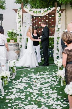 Hannah and Joe exchanged vows at an altar composed of a wooden arch draped with ivory fabric and a garland of verdure and pearl flowers. #weddingceremony #vineyardwedding #ceremonydecor Photography: Clane Gessel Photography. Read More: https://www.insideweddings.com/weddings/rustic-inspired-summer-wedding-at-a-vineyard-in-northern-california/651/