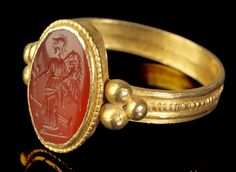 Roman Gold and Carnelian Fortuna Panthea Ring, 2nd-3rd Century ADDepicting the helmeted Fortuna Panthea (goddess of prosperity and good fortune) with wings, cornucopia, rudder, poppies and a corn ear.