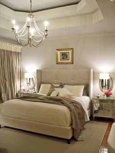 """In this simple yet elegant bedroom, layered, textural neutrals lend interest without drawing attention away from the room's distinctive architecture. """"The use of warm and cool grays was mirrored by the use of warm and cool metallics in the space,"""" says designer Terri Symington. """"The small amount of accent color from the fresh flowers adds the final touch that a neutral monotone color scheme often needs."""""""