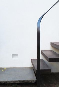 Floating wood stairs, metal ribbon handrail